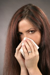 young woman wiping nose